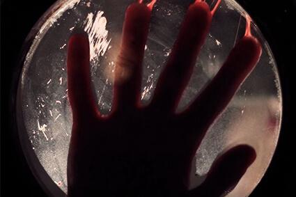 Psychose by Wake Up Lyon Escape Game - Main ensanglantée derrière le hublot dans un asile psychiatrique